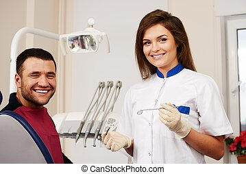 Happy man patient and smiling woman dentist at dental...