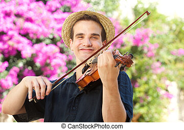 Happy man playing violin outside