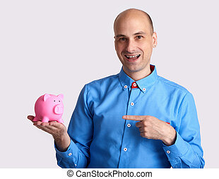 man pointing finger to a piggy bank.