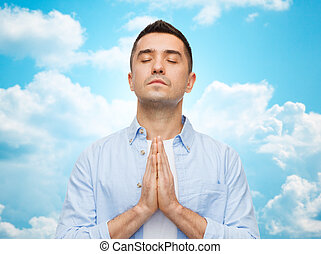 faith in god, religion and people concept - happy man with closed eyes praying over blue sky with clouds background