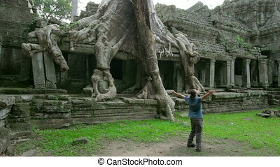 Happy man raised arms in angkor