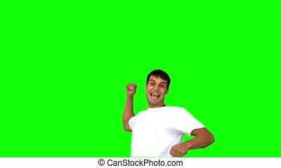 Happy man raising his arm on green screen