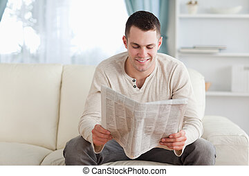 Happy man reading a newspaper