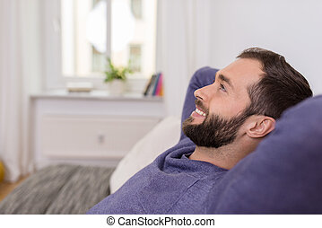 Happy man relaxing at home daydreaming - Happy bearded man...
