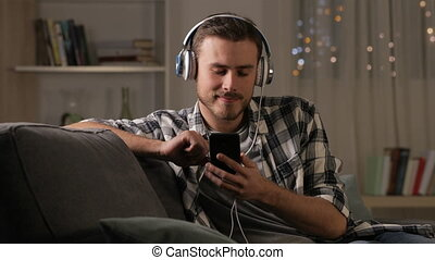 Happy man relaxing listening to music in the night - Happy...