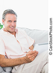 Happy man relaxing on his couch using tablet pc looking at camera at home in living room