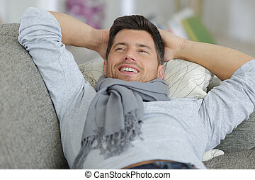 happy man relaxing on sofa at home