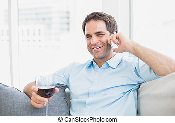 Happy man relaxing on sofa with glass of red wine talking on...