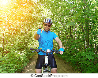 Happy man riding a mountain bike in the green woods.