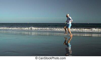 Happy man runs along the ocean beach at sunset. Concept of...