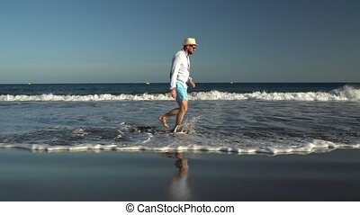 Happy man runs along the ocean beach at sunset. Concept of carefree modern life. Tenerife, Canarian Islands. Slow motion