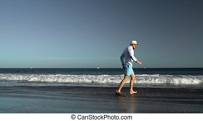 Happy man runs along the ocean beach at sunset. Concept of carefree modern life. Tenerife, Canarian Islands