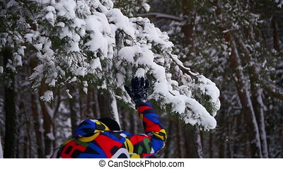 Man Runs and Throws the Snow with Snow-Covered Branches in...