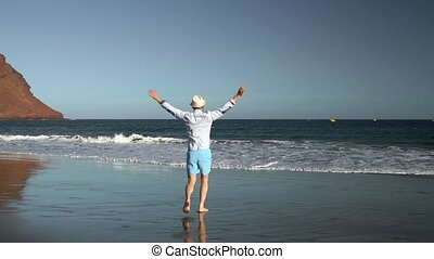 Happy man runs to the ocean beach at sunset. Concept of carefree modern life. Tenerife, Canarian Islands