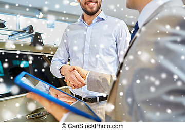 happy man shaking hands in auto show or salon