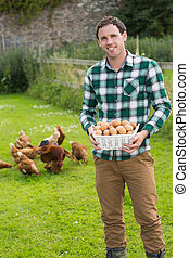 Happy man showing a basket filled with eggs - Proud man...