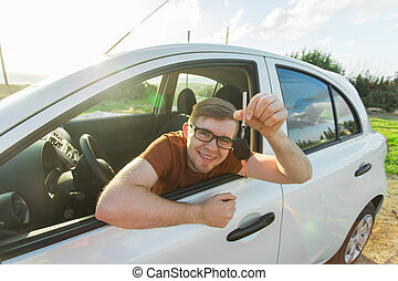 Happy man showing the key of his new car