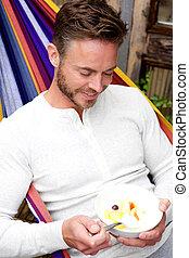 Happy man sitting in hammock eating fruit salad