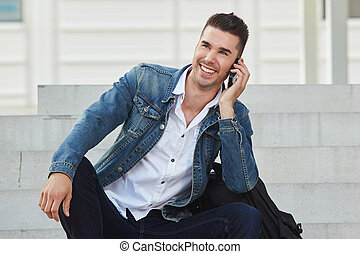 happy man sitting on stairs with mobile phone