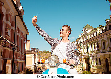 Happy man sitting on the scooter making selfie photo