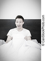 Happy man smiling after masturbation in bed at home