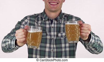 Happy man smiling, holding out two beer mugs to the camera
