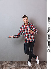 Happy man standing isolated pointing