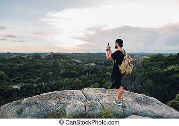 Happy man standing on the big stone and makes photo - Happy...