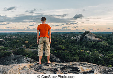 Happy man standing on the big stone in the forest - Happy...