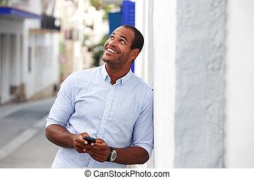 Happy man standing outside on street with mobile phone