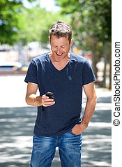 Happy man standing outside with cellphone laughing on sidewalk