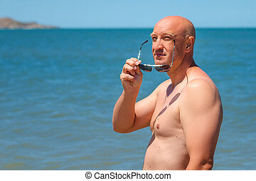 happy man sunbathing standing by the sea holiday concept
