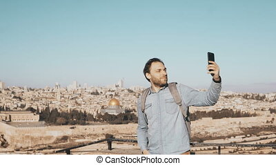 Happy man takes selfie in old town Jerusalem. Bearded local...