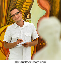 happy man taking notes in an art gallery - cropped view of...