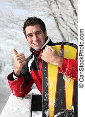 Happy man talking a break from snowboarding