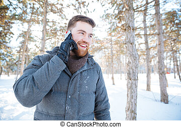 Happy man talking on the phone in winter park