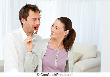 Happy man tasting a tomato while his girlfriend preparing lunch