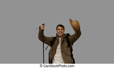 Happy man throwing his hat on grey screen in slow motion