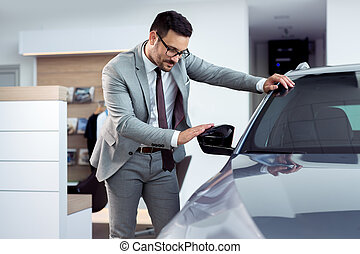 Happy man touching car in auto show or salon
