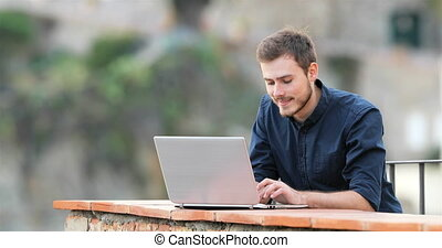 Happy man typing on a laptop in a balcony of a rural...