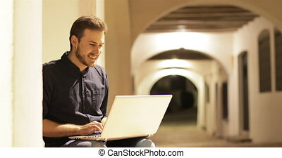 Happy man using a laptop with headphones in the night -...