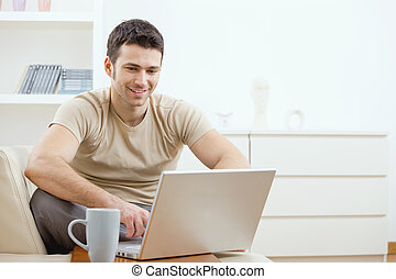Happy man using computer - Happy young man in t-shirt...