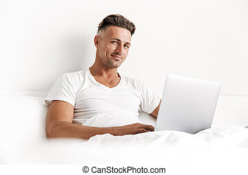 Happy man using laptop computer