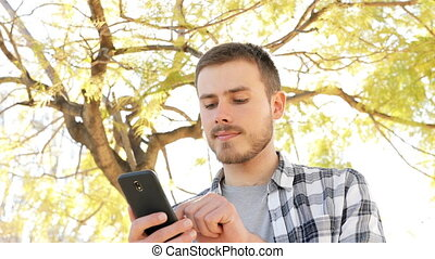 Happy man using smart phone in a park - Portrait of a happy...