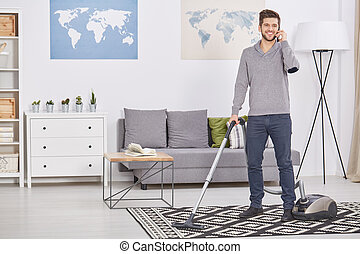 Happy man vacuuming