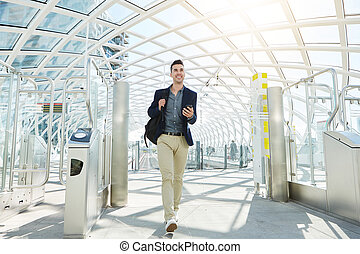 happy man walking by automated turnstile with phone