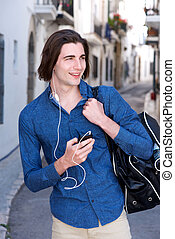 Happy man walking outside with phone and headphones