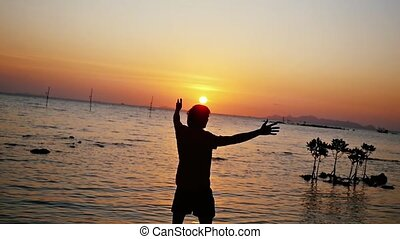Happy man walks on the beach to the sea at amazing sunset raises hands in slow motion.