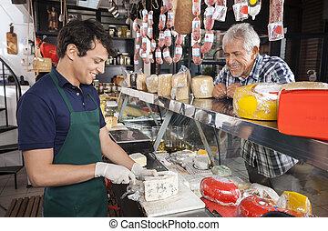 Happy Man Watching Salesman Slicing Cheese In Shop