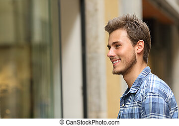 Happy man watching storefront in the street